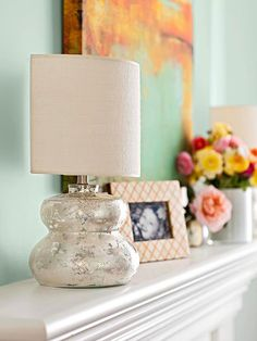 Small mercury-glass lamps add warmth and ambience and eliminate the need for wall sconces. Half shades make it easy to position the lamps close to the wall to ensure that they fit on the shallow mantel. The elegant and almost vintage finish of the lamps adds character and a bit of texture to the room.