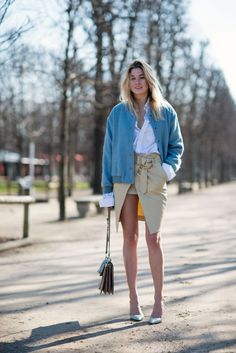 Camille Charrière of Camille Over the Rainbow in a bomber jacket, button-down shirt, wrap skirt, and pumps