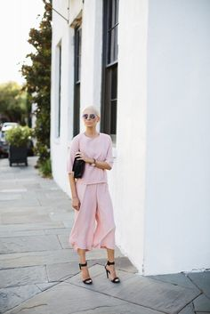 A blush jumpsuit with black sandals and a sleek clutch