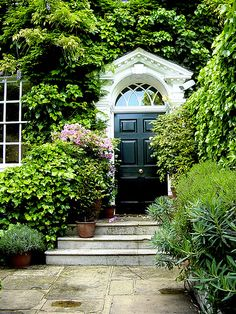 Classical entry with black lacquered door and made mysterious by the encroaching greenery. Habitually Chic®: Happy Summer!