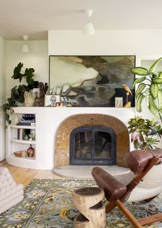 A new, sweeping plaster form flows around the fireplace, elongating the mantel and creating display shelves in a previously unused alcove. The convex tile treatment composed of Clé tile provides a rich contrast with the plaster, and the new hearth is marble. #dwell #portland #beforeandafter #modernhomerenovations