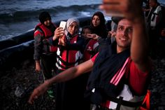 Syrian refugees take selfies moments after arriving on a dinghy on the Greek island of Lesbos, September 14, 2015. Of the record total of 432,761 refugees and migrants who made the perilous journey across the Mediterranean to Europe as of September 2015, an estimated 309,000 people had arrived by sea in Greece, the International Organization for Migration said.