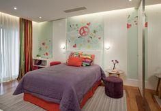 """""""Peace and love"""" foi o tema escolhido pela adolescente para o trabalho da arquiteta Giselle Macedo e da artista plástica e designer Patricia Covolo para seu quarto com 17,5 m². A cabeceira feita de couro e a """"boiserie"""" em madeira destacam a roupa de cama, as almofadas, a cortina e a parede com pintura personalizada"""