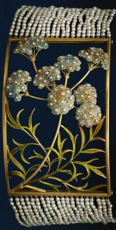 strings of seed pearls attaching to enamelled centrepiece