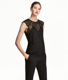 Black. Fitted top in jersey and lace with cap sleeves.