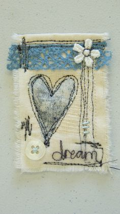 little textile collage, using a hand printed heart and free machined word, machine scribbles and embellishments.