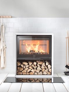 Contura 310G in white with a glass front and log storage. Also available with cast-iron door. #castiron #stove #fireplace #contura300
