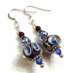 These pretty earrings feature burgundy and blue lampwork beads, blue Swarovski crystals, burgundy Swarovski pearls, sterling silver bead caps, sterling silver spacer beads, Tierra Cast bead aligners and small round sterling silver beads dangling from sterling silver earwires. They measure approximately 1 3/4 inches from the top of the earwire.