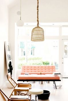 Living room with colorful sofa.Great light fixture takes center stage.  It keeps things light and airy.  Beautiful peach sofa against white walls. #rusticchandelier #whitewalls
