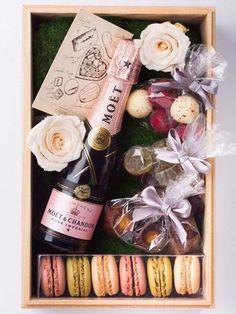 a beautifully assembled gift box featuring champagne, flowers, chocolate and macarons   just add a tag