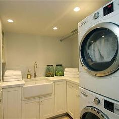 248 Hills Point - laundry/mud rooms - laundry room, laundry room ideas, laundry room sink, farmhouse sink, laundry room cabinets, white marble countertops, white marble backsplash, built in linen cabinet, linen cabinet, glass front linen cabinet, stacked washer dryer, stacked washer and dryer,
