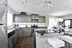 Kitchen with central granite topped island Granite Tops, New Community, Home Builders, New Homes, Island, Architecture, Building, Kitchen, Home Decor