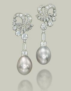 A PAIR OF NATURAL PEARL AND DIAMOND EAR PENDANTS  Each greyish white natural drop-shaped pearl, measuring approximately 13.7-14.8 x 19.1 mm and 13.8-14.5 x 19.0 mm, with a square and baguette-cut diamond surmount, to the baguette and brilliant-cut diamond openwork scroll top, late 1960s, mounted in platinum and gold, 6.0 cm Accompanied by report no. 59112 dated 29 March 2011 from the SSEF Swiss Gemmological Institute stating that the pearls are natural saltwater pearls