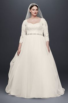 Made for the modern princess, this classic organza plus size ball gown was designed with three-quarter lace sleeves and a flattering sweetheart neckline embellished with over 4,000 beads. The draping