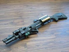 Mossberg 590 (breacher custom) with a factory heatshield and aftermarket magazine extension.  There is a receiver mounted picatinny rail with an MRD or RMR type micro reflex sight.  Also are an Elzetta light mount, tri-railed forend with Magpul AFG and some sort of handstop, a receiver mounted Mesa Tactical shell carrier, and an ATI Akita stock or a Blackhawk Knoxx Compstock which is built on the Hogue stock.