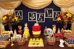 """Dona da empresa Silly and Sweet Party (www.facebook.com/Silly.and.Sweet.Party.Decoration), em  New Milford, Connecticut, nos Estados Unidos, a arquiteta brasileira Alessandra Bianca Schmidt escolheu a animação """"A Bela e a Fera"""", da Disney, como tema para a festa de cinco anos da filha, Alexia, que é fã da história. A decoração atrás da mesa principal foi feita com cortinas douradas e letras de madeira pintadas da mesma cor, formando a palavra """"bela"""", que foram fixadas sobre uma parede azul"""
