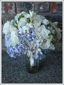 The Flowers:  Light Blue, Lavender & Green Hydrangea, Stephanotis, White Lisianthus, White Dahlias, White Freesia and Variegated Greens    Additional Design Elements:  Small hanging mason jars for the aisle and large mason jars for the centerpieces.    Brides Bouquet:  Light blue and lavender hydrangea with stephanotis, white lisianthus and white freesia.  Wrapped with ivory satin ribbon.