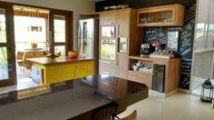 Cozinha americana com ilha amarela e parede com tinta de quadro negro!