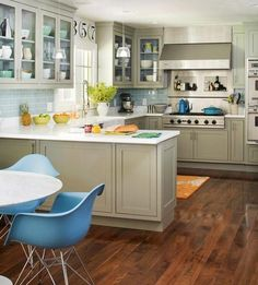 Kitchen with eat in dining. Muddy gray painted cabinets, amazing range, and fun modern blue chairs.