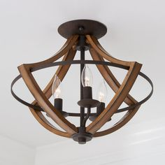 Traditional warmth meets industrial minimalism. The rubbed black edges on the faux wood frame complements the rustic bronze finish of the inner ring. Curved arms and candelabra bulbs add classic charm to the chic simplicity of the drop silhouette. Entry Lighting, Cabin Lighting, Flush Lighting, Rustic Lighting, Interior Lighting, Living Room Lighting Ceiling, Rustic Flush Mount Lighting, Entry Way Lights, Entry Way Lighting Fixtures