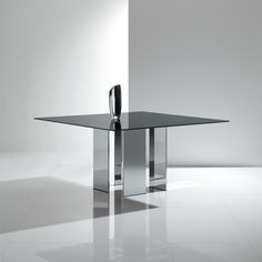 Eyon is a sleek table for the most modern of spaces. This bold, minimal table pairs black lacquered glass with a mirrored metal base for a look that exudes space age elegance.