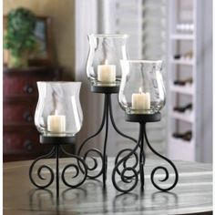 """HURRICANE CANDLE LANTERN TRIO (set)  PRODUCT DESCRIPTION:What a beautiful way to decorate your table! Each of these gorgeous hurricane lanterns features a scrolling black metal stand that holds a glass candle cup at varying heights. Insert the candles of your choice and let the flickering flames shed a lovely glow on your tabletop. (slc)  Large: 6"""" x 6 1/8"""" x 12"""" high;  Medium: 5 1/2"""" x 5 1/8"""" x 10"""" high;  Small: 5"""" x 4 5/8"""" x 8 1/4"""" high. UPC Number:849179015053  Material(s):GLASS, IRON"""