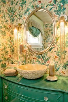 Bold bathroom decor, painted teal dresser, crystal sconces, bird print wallpaper