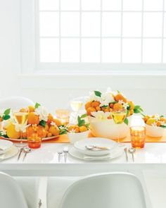 """Juicy winter citrus fruit was the inspiration behind this cheery duo. To replicate the centerpiece (which was created by Quatre Coeur), fill white bowls and platters with navel oranges, clementines, and kumquats. For contrast, add lemon leaves and white gardenias, orchids, and stephanotis. Complete the look with an orange table runner and water glasses. The Details: Richard Ginori """"Eclissi Platinum"""" dinnerware and """"Oblique"""" wineglasses. Cutipol """"Moon"""" flatware (shophorne.com)."""