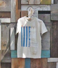 太陽光を利用したシルクスクリーンでの手刷りのTシャツ。 ブルーのストライプペイントの上にコッパー(銅色)のロゴと白のロゴをプリントしました。ガーゼのコラージュ...|ハンドメイド、手作り、手仕事品の通販・販売・購入ならCreema。