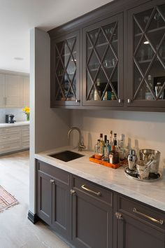 light grey cabinets in kitchen, dark grey cabinets at wet bar