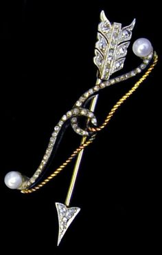 An early Victorian diamond-set arrow and bow brooch, circa 1840. The arrow point and feathers set with rose-cut diamonds, the bow set with two 3mm pearls and rose-cut diamonds, the arrow detachable from bow. #Victorian #brooch