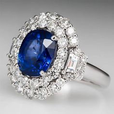 This magnificent oval sapphire ring is centered with a carat natural blue sapphire. Accenting the sapphire are two trapezoid cut diamonds and two halos of round brilliant cut diamonds. The sapphires color is phenomenal and the trapezoid cut diamond Sapphire Wedding Rings, Blue Sapphire Rings, Sapphire Jewelry, Sapphire Gemstone, Blue Rings, Sapphire Birthstone, Gemstone Rings, Diamond Jewelry, Ring Verlobung