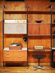 An original Nelson CSS system is outfitted with a Rek-ko-kut record player designed by the Nelson office and paired with an Eames Wire Chair...