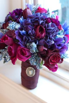 purple hydrangea, purple and blue anemones, black baccara roses, mamy blue roses, agapanthus, and blue muscari dipped in glitter of course