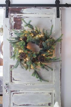 Christmas wreath on a barn door with chippy paint