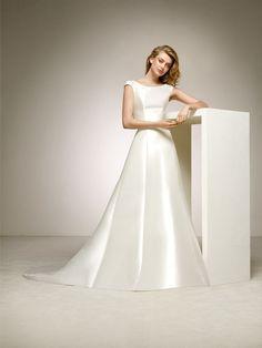 """Modelo Delirio Pronovias. """"Se gosta de mikado, ficará encantada com este maravilhoso vestido de noiva clássico com saia de corte em A; um modelo marcado pelo volume da saia e as linhas mais discretas nos decotes em barco e nas costas redondas. Um daqueles vestidos tanto sóbrios como femininos."""""""