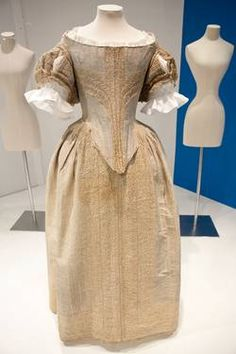 The dress (bodice and skirt) is of silver tissue trimmed with cream parchment lace, c 1660.