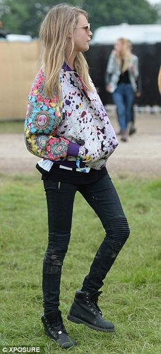 Cara Delevingne does casual cool in a printed bomber jacket, skinny jeans and black boots at Glastonbury Festival #Glasto