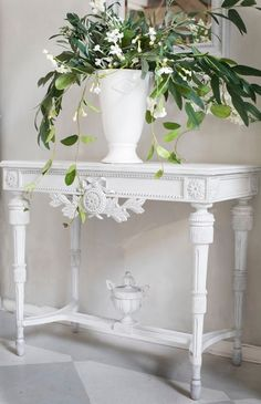 Sweet white French inspired side table with flowing floral arrangement.