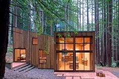 This small house in the redwood forest of Sea Ranch in California is a great example of a building that integrates itself through the use of wood over the whole exterior. Small windows predominate on the upper exterior, but a large window off the living area brings the forest inside.