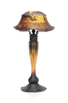A DAUM CAMEO GLASS TABLE LAMP EARLY 20TH CENTURY The shade overlaid and acid-etched with sailing boats on a lake with trees in the foreground, the base with pine needle decoration, signed in cameo on shade Daum Nancy with Cross of Lorraine 20½ in. (52 cm.) high
