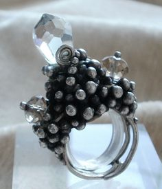 ring made entirely by hand, with granulation and three crystals of two colors,