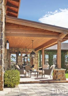 A protected outdoor living area features cushioned metal furniture from Thos. Baker in Bainbridge Island, Washington, and Paul Ferrante's overhead lanterns from John Brooks.