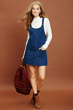 A denim shift dress featuring a scoop neckline, two front pockets, a button front, and a sleeveless cut.