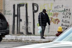 A pedestrian walks by graffiti in downtown Detroit