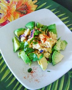 Scrambled eggs topped with avocado and cilantro. Also turkey bacon.