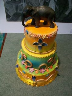 Teal, orange and yellow airbrushed, Indian inspired cake with gold swirls and elephant topper