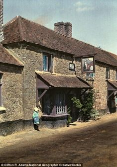 1931, Devon: A child stands by The Cat and the Fiddle Inn, next to the old Roman road in Exeter