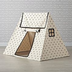 This sturdy white playhouse provides the perfect foundation for any kid's imaginary adventures. It features a stylish print, roll-up door and cutout windows.