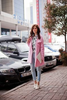 Shop this look on Lookastic: http://lookastic.com/women/looks/button-down-shirt-and-overcoat-and-clutch-and-skinny-jeans-and-plimsolls/1457 — White and Black Print Button Down Blouse — Pink Coat — White Leather Clutch — Light Blue Skinny Jeans — White Plimsolls
